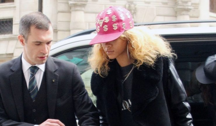 Rihanna wearing pink Joyrich dollar sign hat