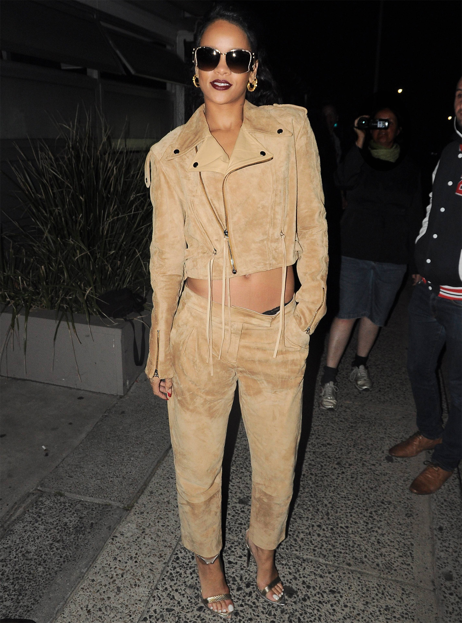 Rihanna in Sydney wearing Holmes & Yang cropped leather moto jacket and suede trousers with Roberto Cavalli snakeskin sandals
