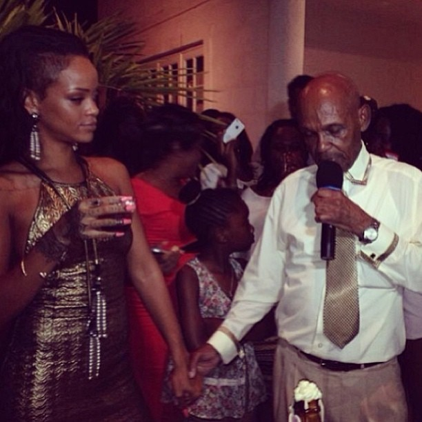 Rihanna at her grandfather's party in Barbados wearing Rihanna for River Island gold textured mini dress and Lanvin metropolis pearl and crystal tassel earrings and necklace