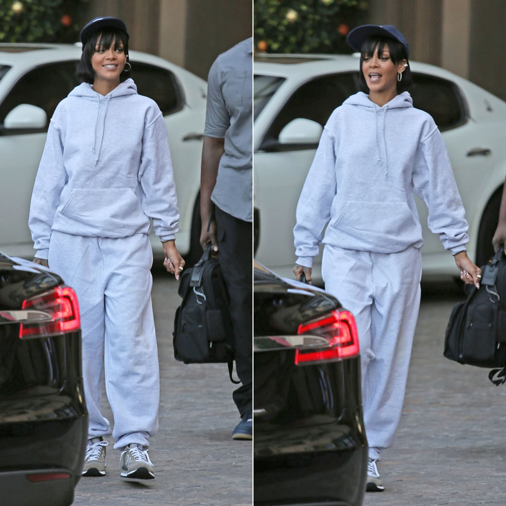 Rihanna in Joyrich gray sweatpants and hoodie, New Balance 574 sneakers, Fila snapback cap