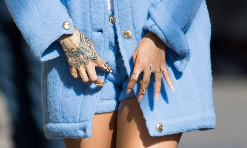 Rihanna wearing Ruby Stella yellow gold and diamond family tree ring, marquise bar ring, double triangle ring and long v ring