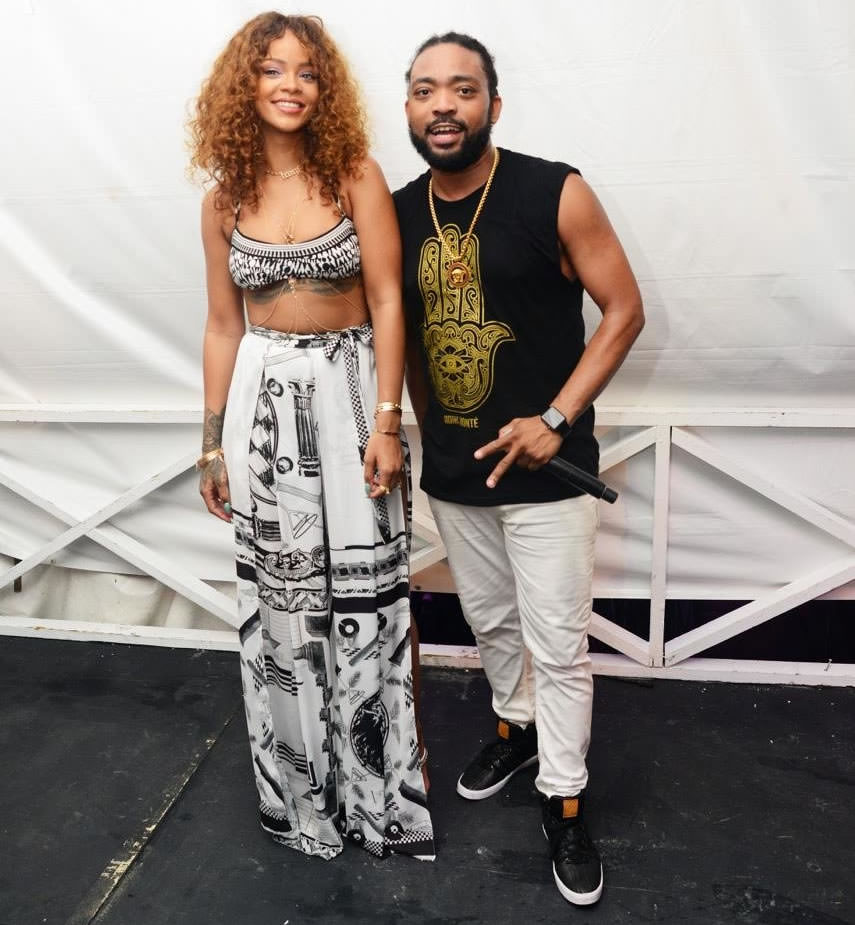 Rihanna with Machel Montano at 1Love concert in Barbados wearing Versus Versace abstract print wrap wide leg split pants