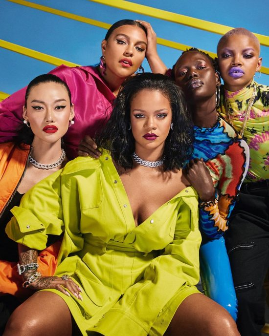 Rihanna posing with models in Fenty Beauty advertisement