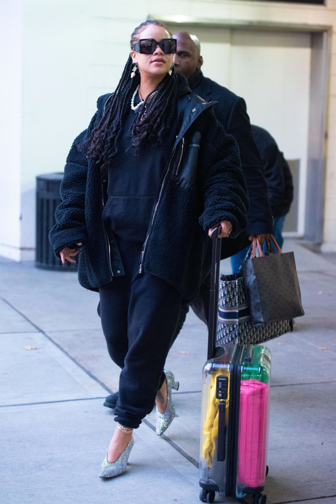 Rihanna crystal pumps airport Bottega Veneta Almond shoes and The Pouch clutch, Celine square sunglasses and Vertical Cabas Tote, Jiwinaia 69 pearl drop earrings, Mastermind reversible fleece jacket, Rimowa x Off-White clear suitcase, Dior book tote, Prada x Adidas white bowling bag