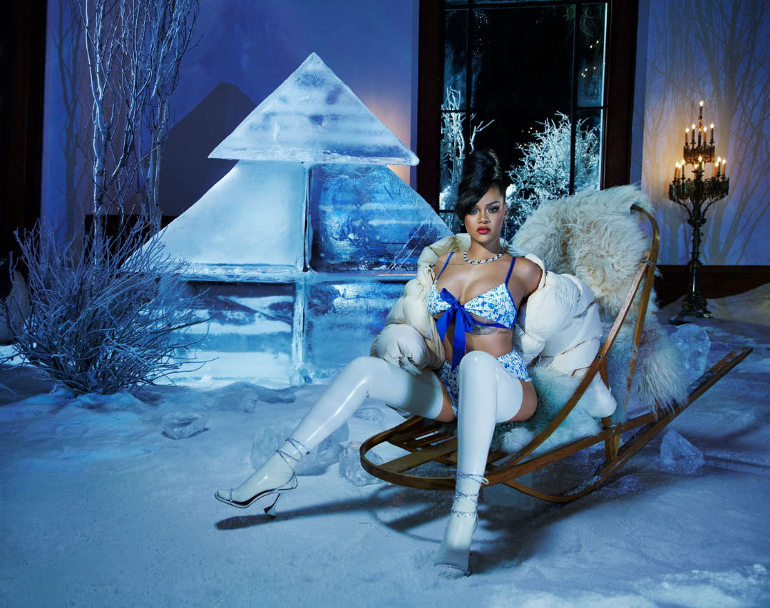 Rihanna blue bow bra Savage Fenty, Atsuko Kudo latex white gloves and stockings, Ding Yun Zhang white puffer coat, Amina Muaddi Vita crystal sandals, Hammerman ceylon flower earrings, Lang Antiques diamond sapphire necklace, XIV karats anklet and body chain